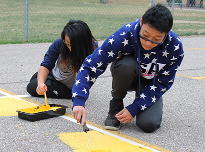 PCSD high school students painting at playground