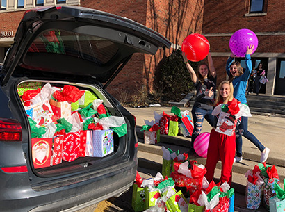 Students packing a car with gifts as part of Stuff Mrs. Armstrong's office