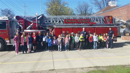 Students pose for a picture with Firefighters in front of a Parma Heights Fire Truck