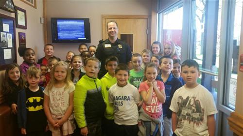 Students pose for a picture with a police officer at the police department