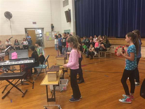 Elementary students standing on risers and at xylophones preparing to perform