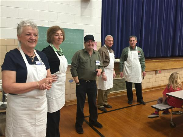 Five members of the Parma Rotary club, wearing white kitchen aprons, standing together.