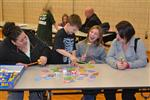 Students playing games with their teachers and families in the school gymnasium.